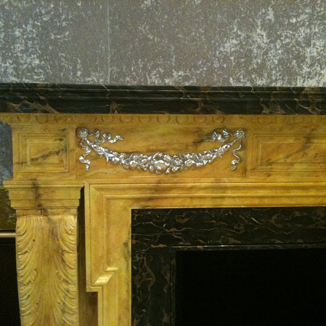 Marbled fireplace with silk velvet wall covering and gilding